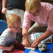 James helps a little boy with his clay model.